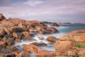 Photo en pose lente de la mer s'écrasant sur les rochers de la côte de granit rose pendant un stage photo près des Sept-Iles en Bretagne